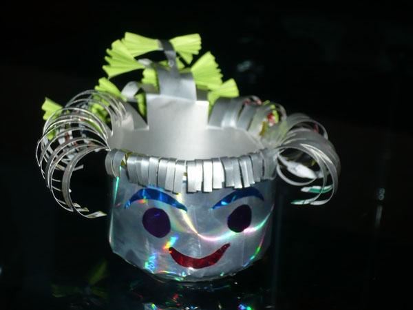 小花朵 制作材料:矿泉水瓶、颜料、吸管 制作方法:把矿泉水瓶的底部接其轮廓剪下用来做花,把瓶的身部剪成叶子形状,分别涂上颜色,然后再花的中间用钉子打孔将吸管插入即可。  抽纸盒 制作材料:空药盒、包装纸 制作方法:在盒的平面取中剪一条和抽纸宽度相近的缝隙,然后用包装纸进行包装盒装饰(包装盒盖不要封住,以免无法放入抽纸。)  美丽的垃圾箱 制作材料:废旧纸壳、彩色贴纸 制作方法:把旧纸壳剪成房子的各个面,然后粘贴在一起,在用彩纸装饰。  可爱娃娃 制作材料:易拉罐、彩纸 制作方法:把易拉罐的上面用剪刀剪下